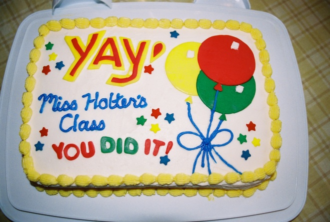 """White rectangle sheet cake with yellow shell trim that says """"Yay! Miss Holter's Class, You Did It!"""""""