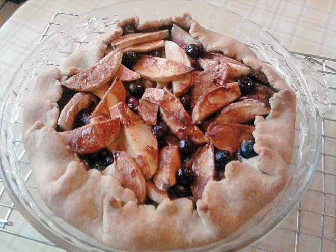 Rustic apple pie with blueberries in a glass pie plate