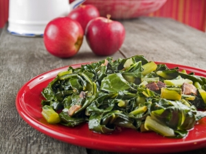 cooked collard greens with bacon on a red plate with apples in the background