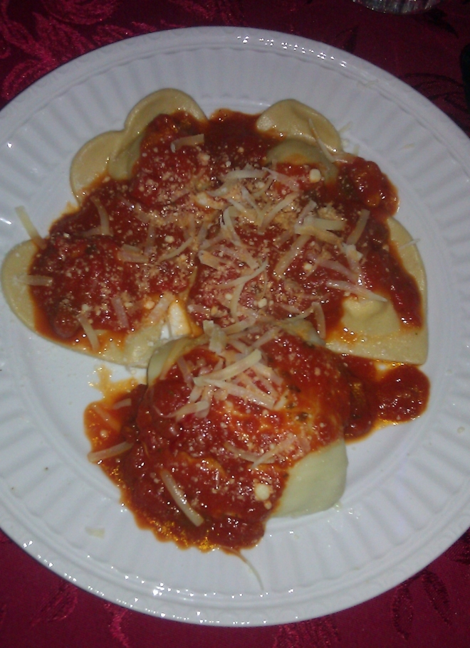 Heart-shaped ravioli and chicken parmesan with red sauce on a white plate.
