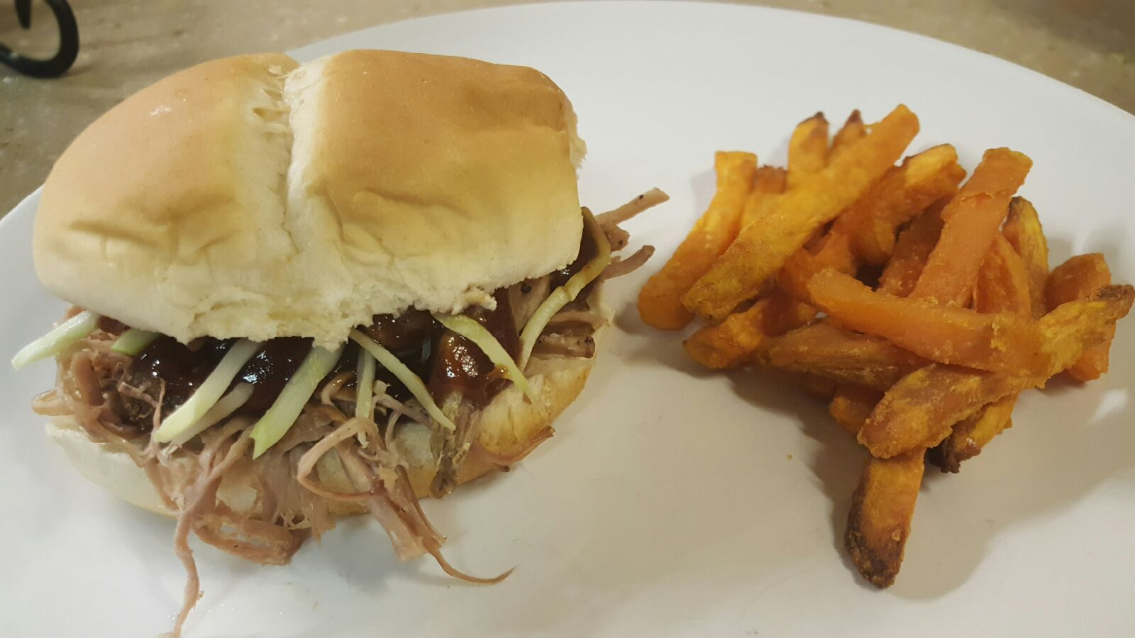 Pulled pork sandwich on a white plate with sweet potato fries.