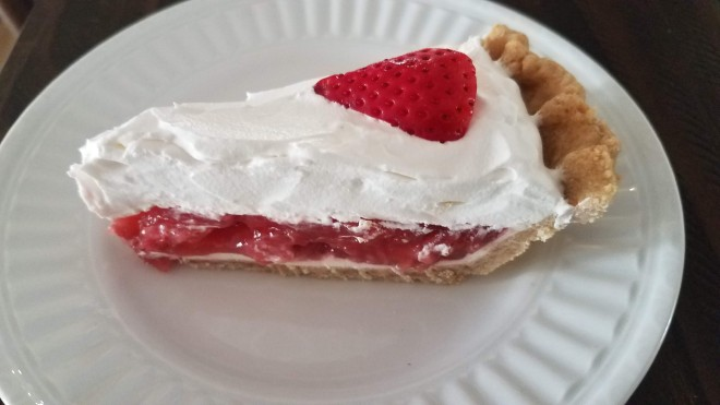 Slice of strawberry pie on a white plate.