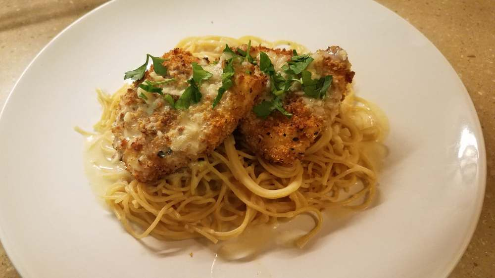 Two pieces of fried chicken breast with lemon sauce over angel hair pasta